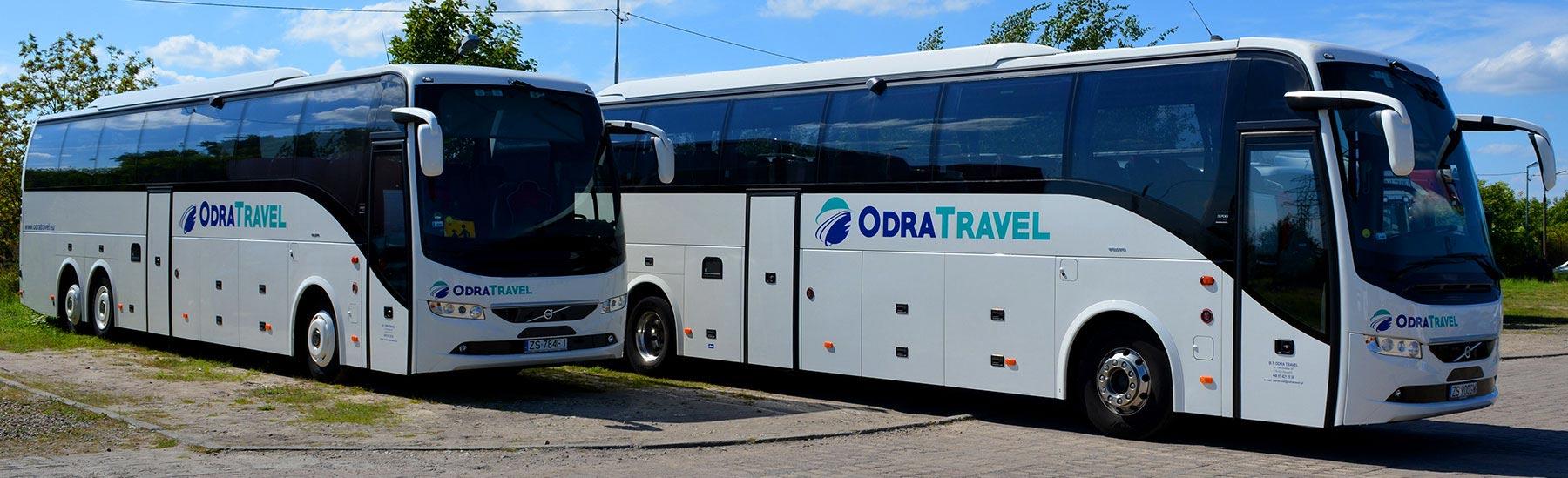 dwa autobusy na parkingu oklejone logiem biura podroózy ODRA TRAVEL