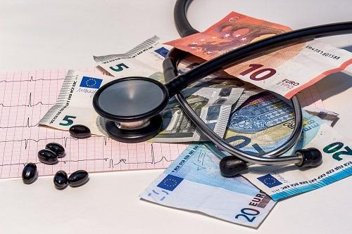 stetoskop na tle tabletek wyników badań i pieniędzy - obrazujący koszty leczenia za greanicą