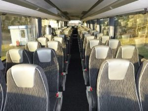 Szare fotele z siwymi zagłówkami w autobusie turystycznym. Wynajmij autobus.