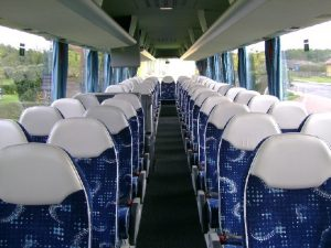 Granatowe fotele z białymi zagłówkami w autobusie turystycznym. Wynajmij autokar.