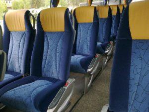 Granatowe fotele z żółtymi zagłówkami w autobusie turystycznym. Transport dla grup.