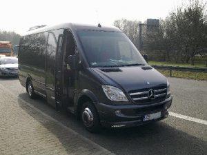 Czarny bus Mercedes na parkingu. Oferta wynajmu transportu.