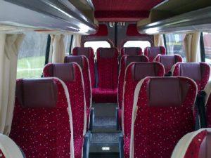 Czerwone fotele pasażerów w busie. Oferta wynajmu transportu.