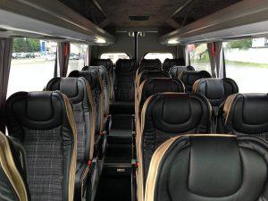 Czarne fotele we wnętrzu busa przeznaczonego na wynajem.