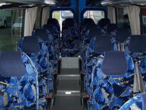 Granatowe fotele we wnętrzu busa przeznaczonego na wynajem.