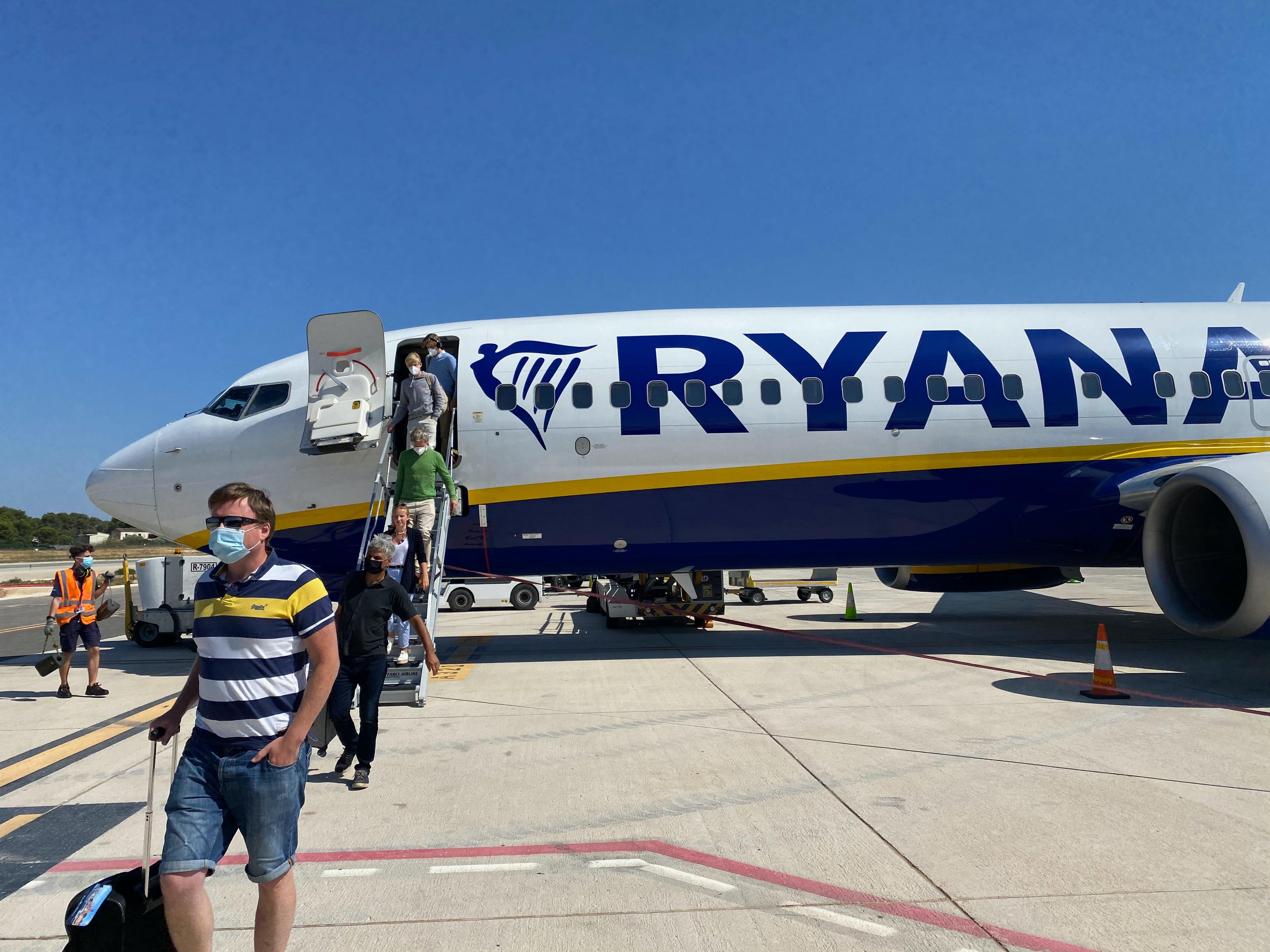 podróż podczas covid-u, z samolotu wychodzą ludzie w maseczkach z bagażem podręcznym