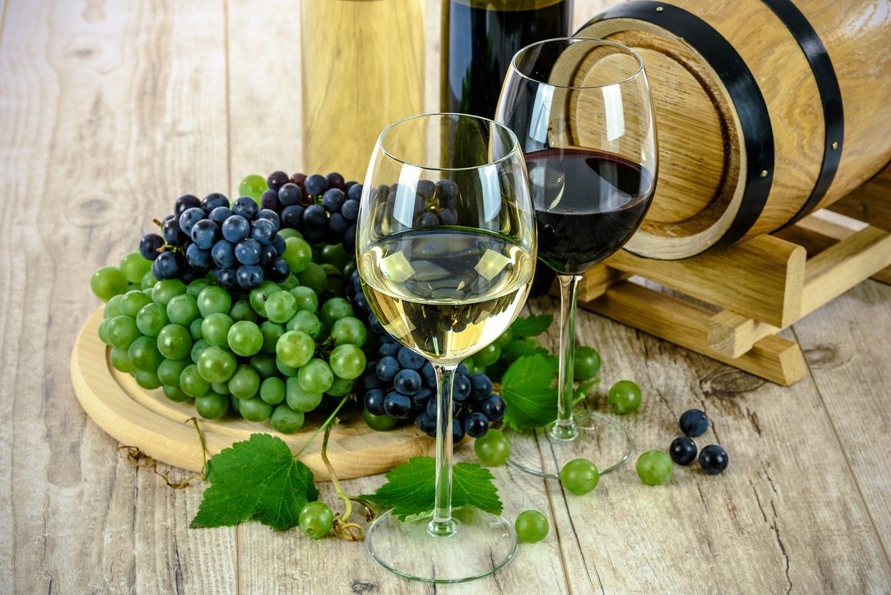 kieliszek białego i czerwonego wino obok winogron i małej beczki